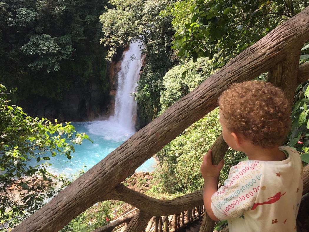 Kleines Kind betrachtet einen Wasserfall