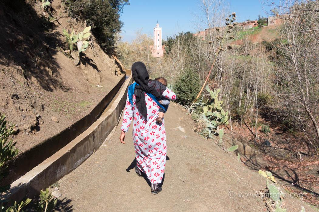Frau mit Kind geht entlang Bewässerungskanal