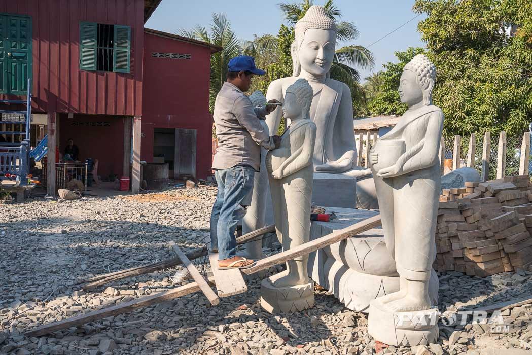 Ein Steinmetz stellt Buddha Statuen her